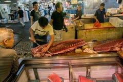Man att klippa en fisk på den Tokyo fiskmarknaden Royaltyfri Bild