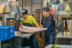 Man att klippa en fisk på den Tokyo fiskmarknaden Arkivfoto
