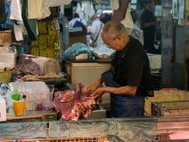 Man att klippa en fisk på den Tokyo fiskmarknaden Royaltyfri Foto