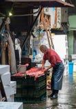 Man att klippa en fisk på den Tokyo fiskmarknaden Arkivbild