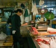 Man att klippa en fisk på den Tokyo fiskmarknaden Royaltyfria Bilder