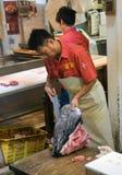 Man att klippa en fisk på den Tokyo fiskmarknaden Arkivbilder