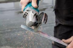 Man att klippa en metallstång med en cirkelsåg Royaltyfria Bilder