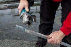 Man att klippa en metallstång med en cirkelsåg Arkivfoto