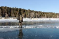 Man att kliva över en spricka på tunn is av en djupfryst flod fotografering för bildbyråer