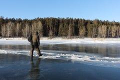 Man att kliva över en spricka på tunn is av en djupfryst flod arkivfoton