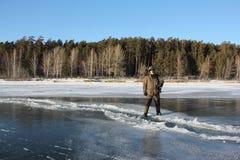 Man att kliva över en spricka på tunn is av en djupfryst flod royaltyfria bilder