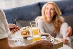 Man att komma med magasinet med den smakliga frukosten till den lyckliga blonda kvinnan Royaltyfri Foto