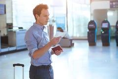 Man att kontrollera logipasserandet och nummer av porten i flygplatsen arkivfoton