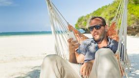 Man att koppla av i en hängmatta på stranden på ferier. Royaltyfri Fotografi