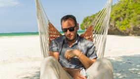 Man att koppla av i en hängmatta på stranden på ferier. Han är lyssnar Royaltyfri Fotografi