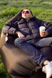 Man att koppla av i en uppblåsbar soffa i höst Royaltyfria Bilder