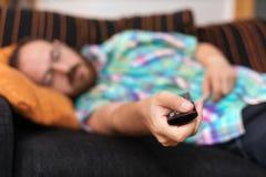 Man att koppla av i soffa med hållande ögonen på tv för fjärrkontroll Grund dof-fokus på fjärrkontroll royaltyfri bild