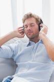 Man att koppla av, medan lyssna till musik på en soffa Fotografering för Bildbyråer