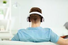 Man att koppla av på soffan och att lyssna till musik bakgrund isolerad white Royaltyfri Fotografi