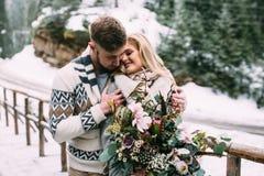 Man att krama kvinnan på träbron i berg Arkivfoto