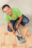 Man att lägga keramiska golvtegelplattor - att klippa ett stycke Arkivbilder
