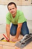 Man att lägga keramiska golvtegelplattor i en nybygge Royaltyfria Bilder