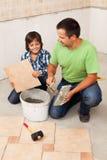 Man att lägga keramiska golvtegelplattor som hjälps av den lilla pojken Royaltyfri Bild
