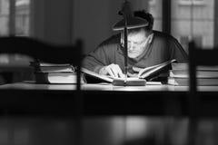 Man att läsa en bok i arkivet under lampan Royaltyfri Fotografi