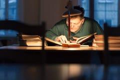 Man att läsa en bok i arkivet under lampan Arkivfoto