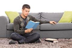 Man att läsa en bok som placeras på golvet av en soffa arkivfoto