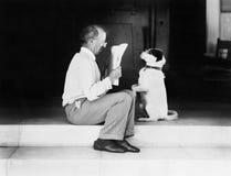 Man att läsa en tidning med hans hund (alla visade personer inte är längre uppehälle, och inget gods finns Leverantörgarantier de Royaltyfri Bild
