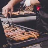 Man att laga mat läckra saftiga köttkorvar på det utomhus- gallret Arkivbild