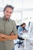 Man att le i idérikt kontor med vikta armar Fotografering för Bildbyråer