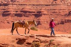 Man att leda en häst i monumentdalen royaltyfri foto