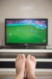 Man att lägga ner på en hemmastadd hållande ögonen på fotbollsmatch för soffa Royaltyfria Bilder