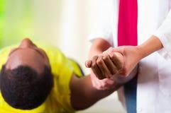 Man att ligga få ner fysisk skuldrabehandling från den physio terapeuten, patienten som ser in i kamera medan henne händer royaltyfri foto