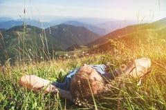 Man att ligga i högt grönt gräs på bergmedaowen arkivbild