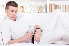 Man att ligga på det smsande meddelandet för soffan på mobiltelefonen Fotografering för Bildbyråer