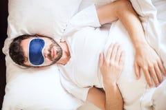 Man att ligga på en säng med sömnmaskeringen Fotografering för Bildbyråer