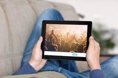 Man att ligga på soffa- och innehaviPaden med App Twitter på set Royaltyfri Bild