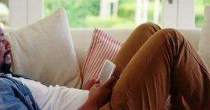 Man att ligga på soffan och den digitala minnestavlan i vardagsrum arkivfilmer