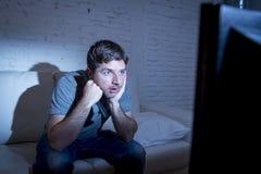 Man att ligga på soffan på fjärrkontroll för tv för vardagsrum som hållande ögonen på hållande ser hypnotiserad Royaltyfri Foto