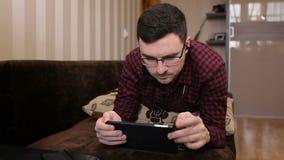 Man att ligga på soffan som lyssnar till musik och hemma använder minnestavlan i vardagsrummet lager videofilmer