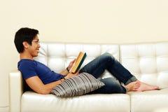 Man att läsa en bok, medan koppla av på soffan Royaltyfri Foto