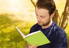 Man att läsa en bok som är utomhus- i trädgården Royaltyfria Bilder