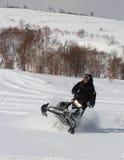 Man att luta snövesslan rätt över i det backcountry Arkivbilder