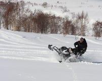 Man att luta snövesslan rätt över i det backcountry Royaltyfri Bild