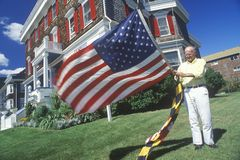 Man att lyfta amerikanen och Maryland flaggor, Cape May som är nytt - ärmlös tröja Royaltyfri Fotografi