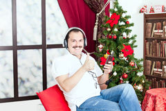 Man att lyssna till musik på hörlurar nära ett julträd Arkivfoton