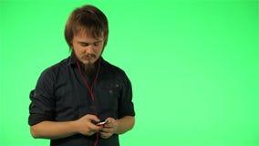 Man att lyssna till musik på telefonen på en grön skärm stock video