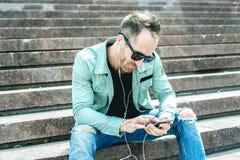Man att lyssna till musiken med earbuds från a Arkivfoto