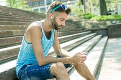 Man att lyssna till musiken med earbuds från a Arkivfoton