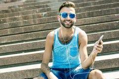 Man att lyssna till musiken med earbuds från a Fotografering för Bildbyråer