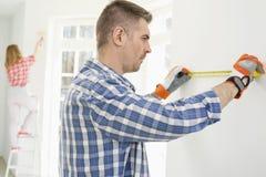 Man att mäta väggen med kvinnamålning i bakgrund Arkivbild